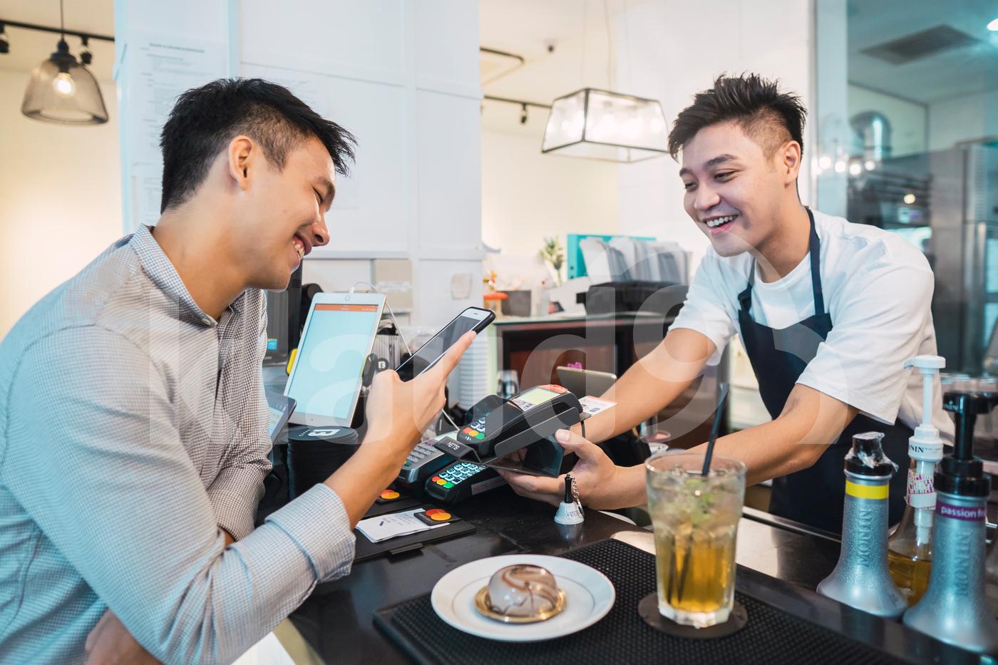 Asian man scanning QR code to make payment