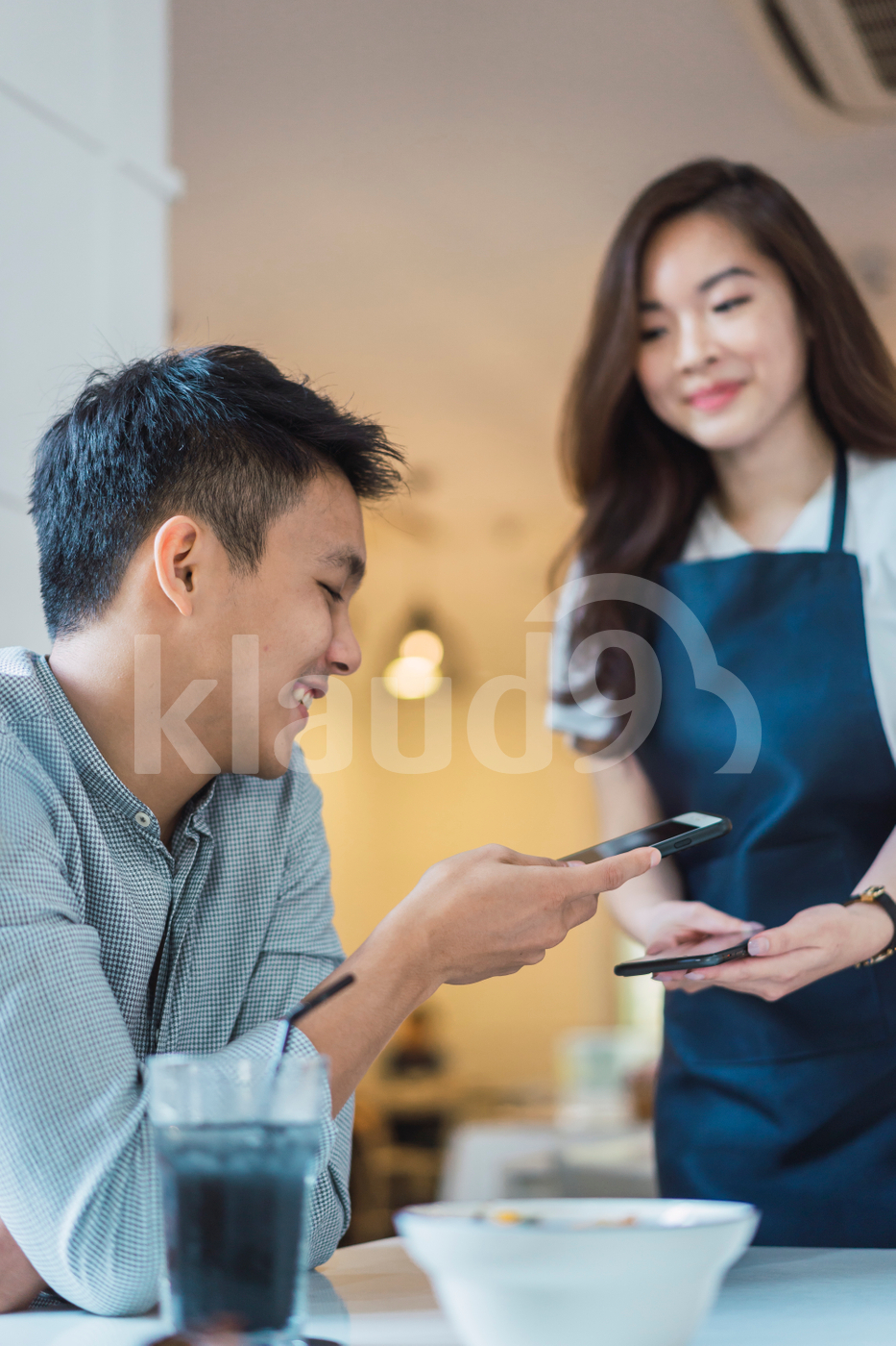 Asian man making payment with mobile in a coffee shop