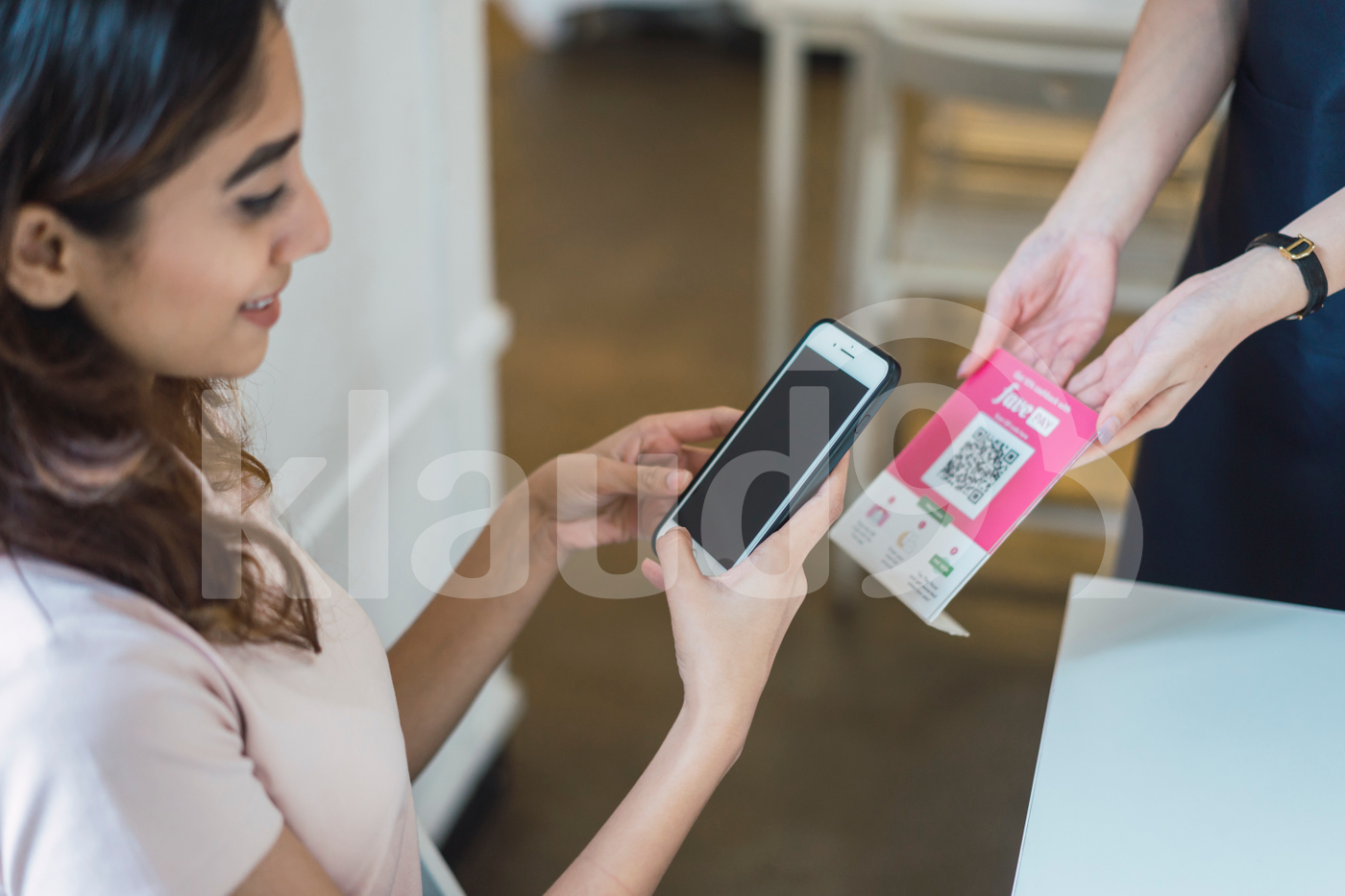 Young Asian woman scanning QR code at table