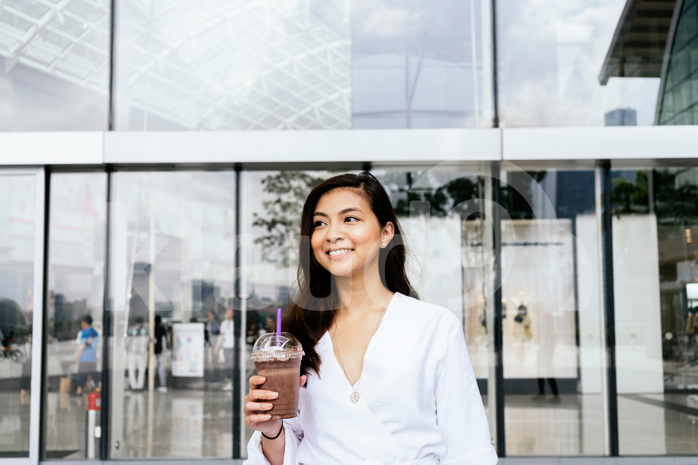 Young adult Asian woman standing in the mall holding drink cup
