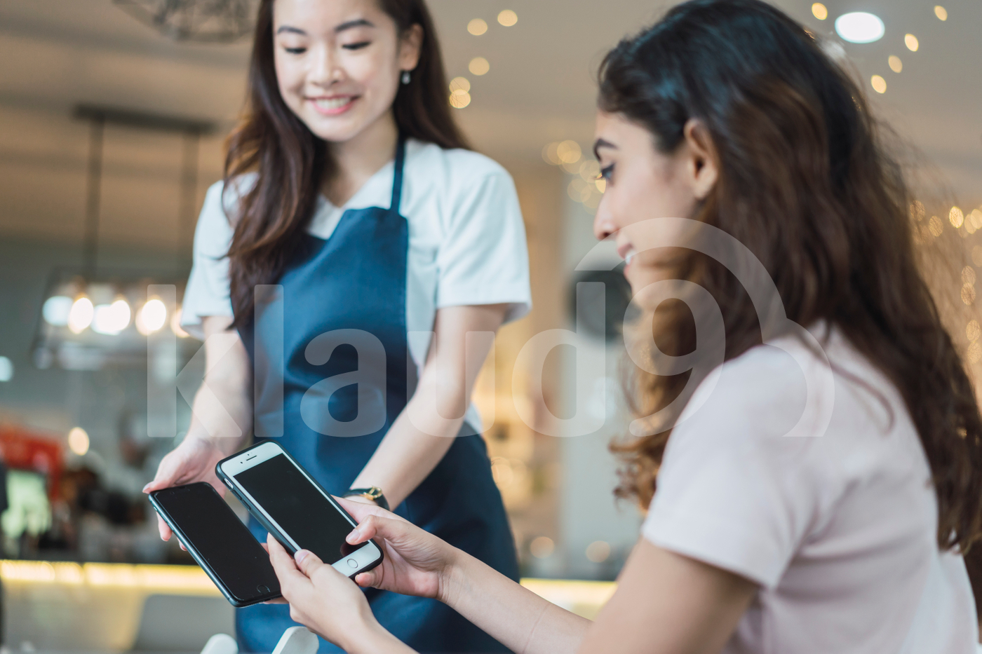 Young adult woman making payment through smartphone at restaurant