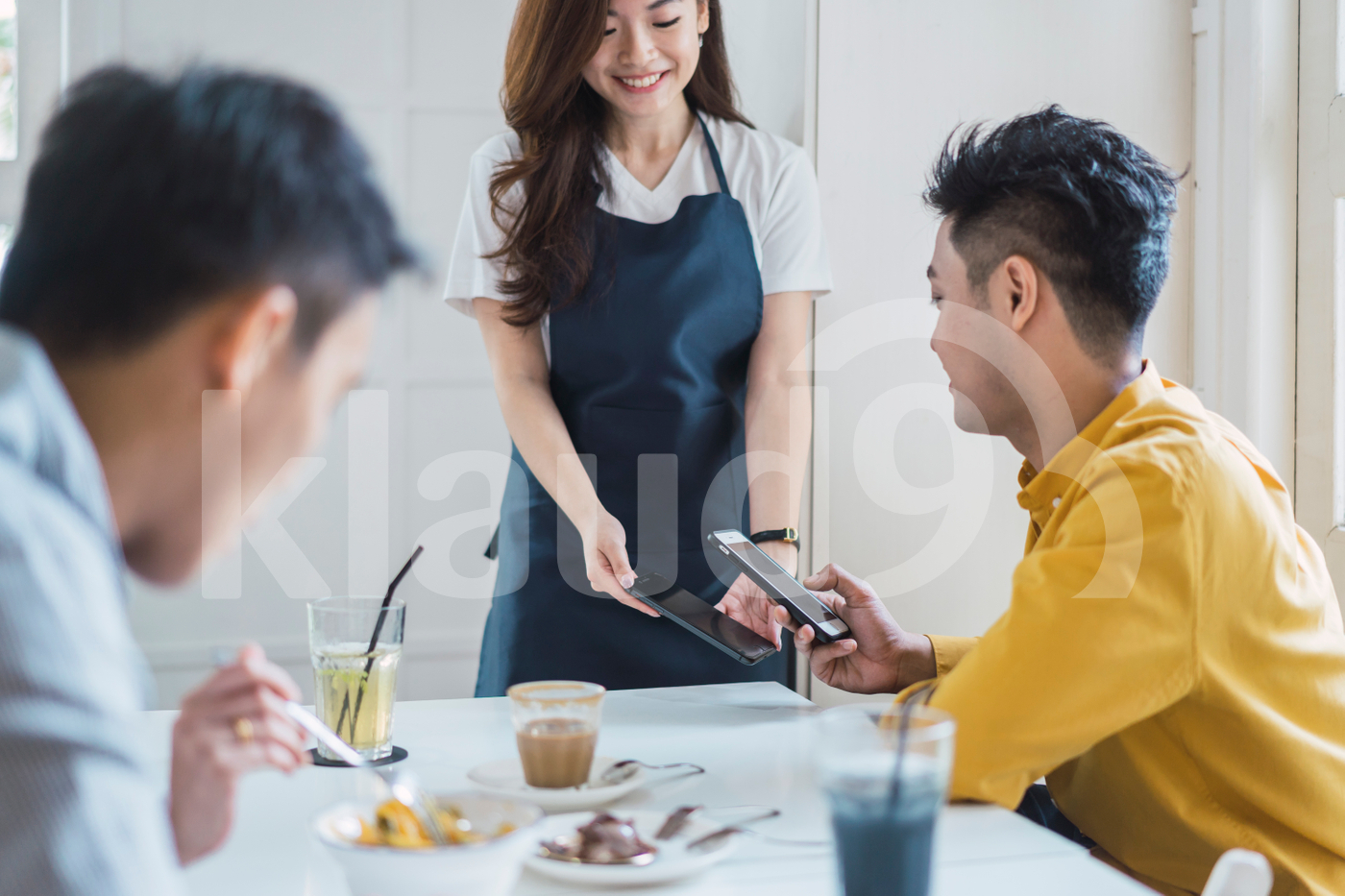 Asian man paying bill through smartphone using e-wallet payment in a coffee shop