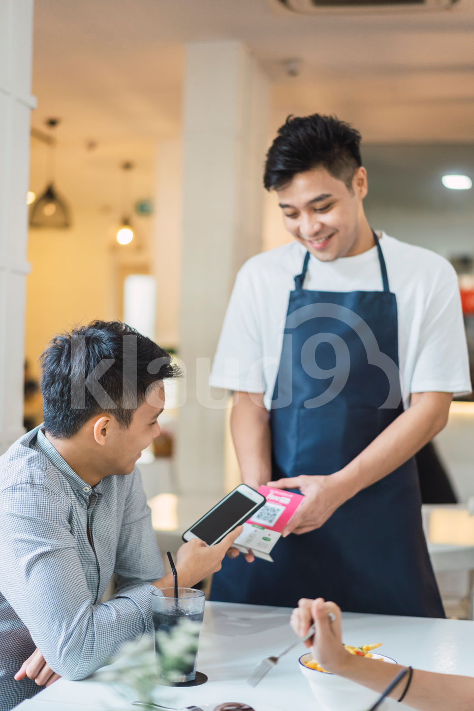 Young Asian man making payment with mobile at table