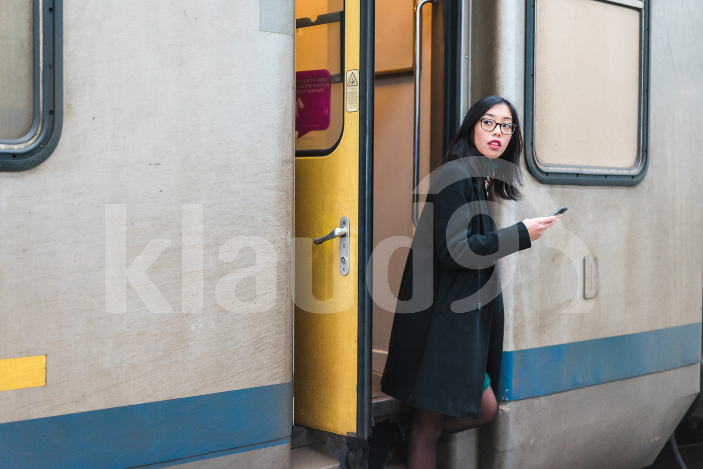 Asian millennial stepping off a train holding her mobile
