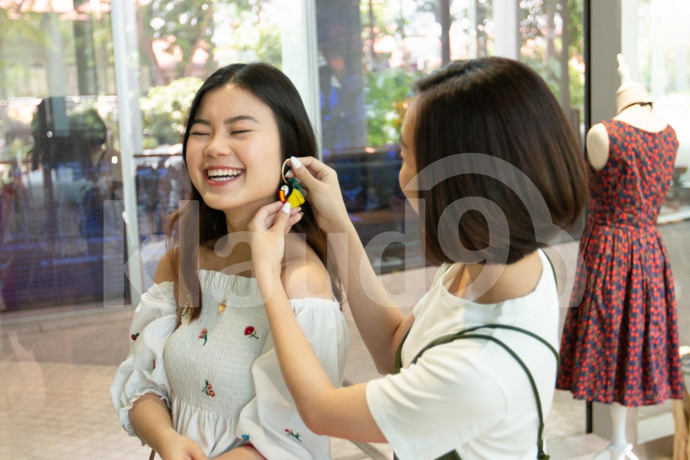 Young Asian women trying earrings on in a shop