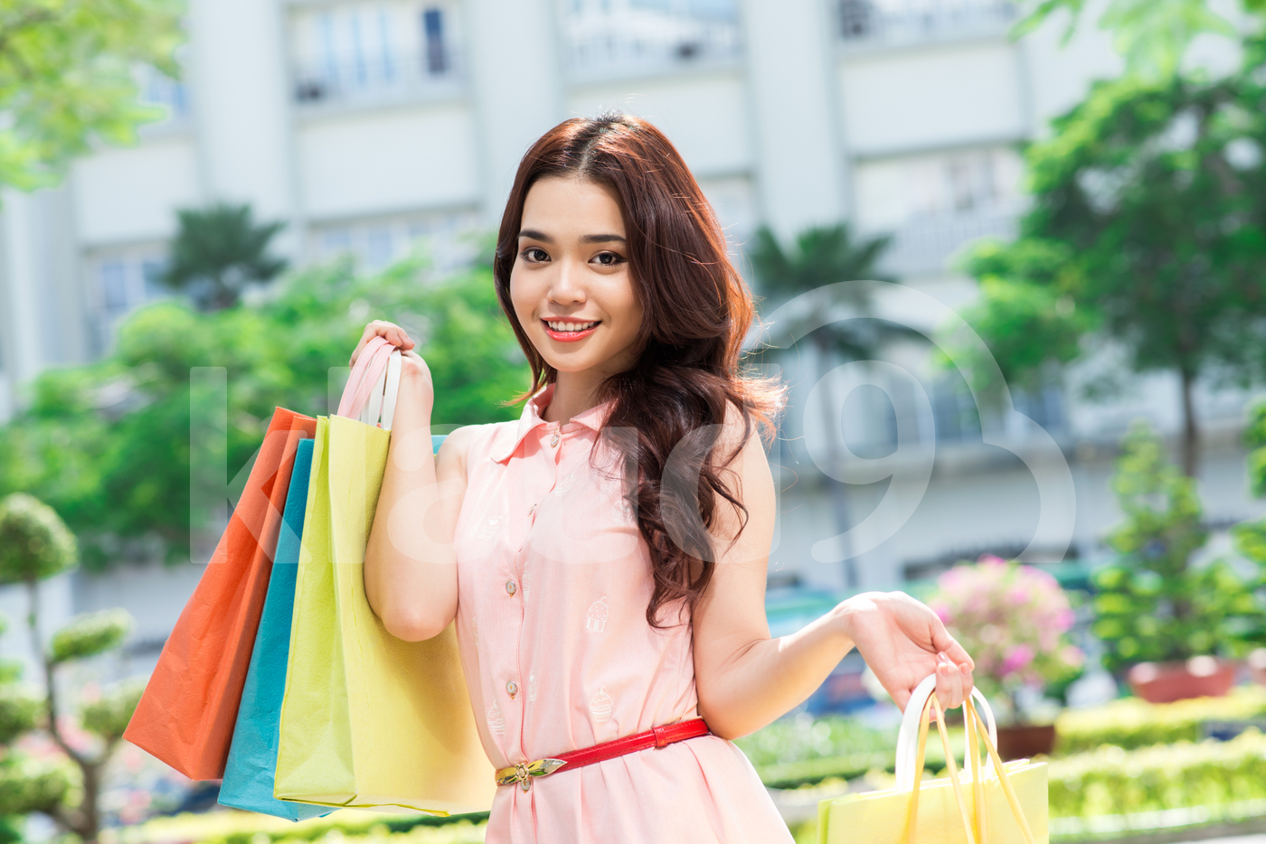 Portrait of a young asian girl with shopping bags outdoors Portrait
