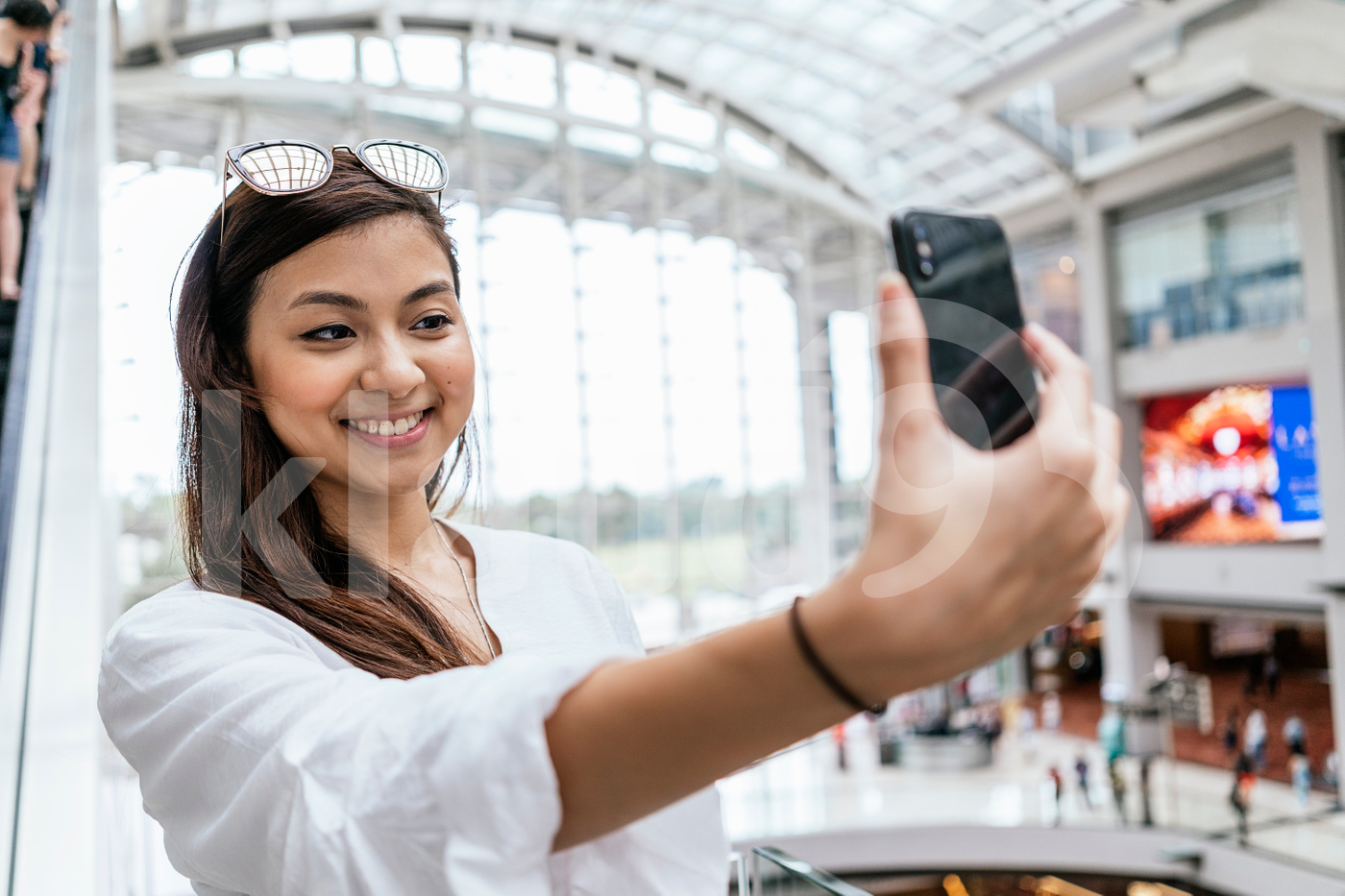 Asian woman posing for a selfie in a mall