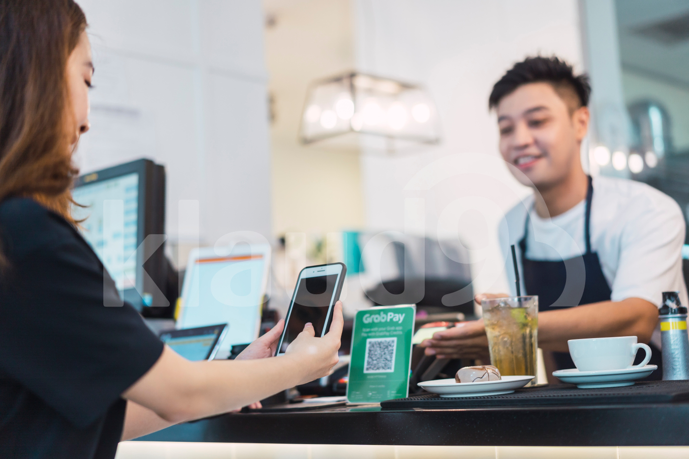 Young Asian woman making payment with mobile at coffee shop