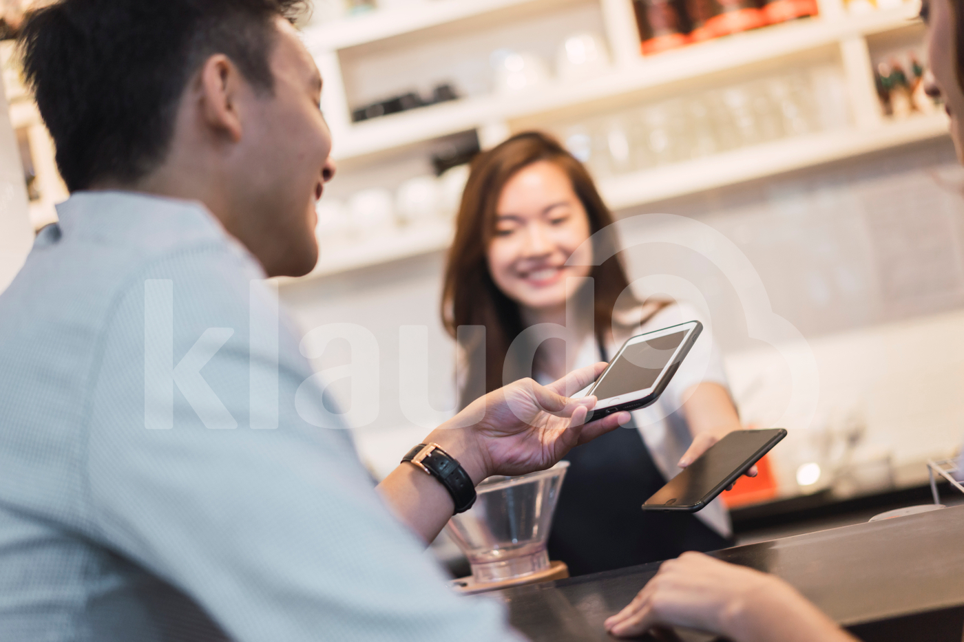 Young man making payment with contactless payment in a coffee shop