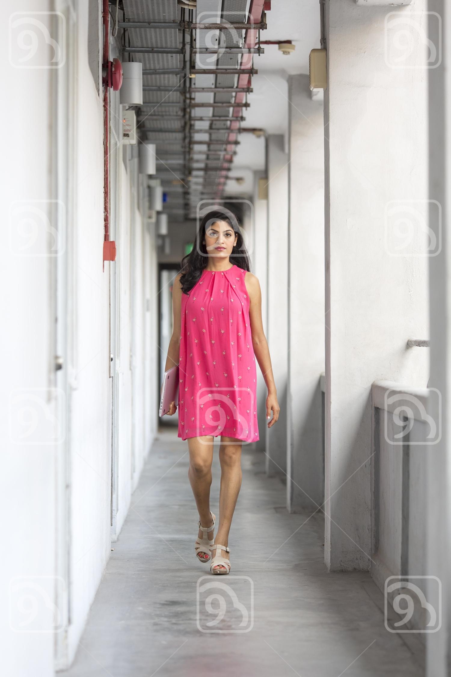 Beautiful Indian lady walking along the corridor