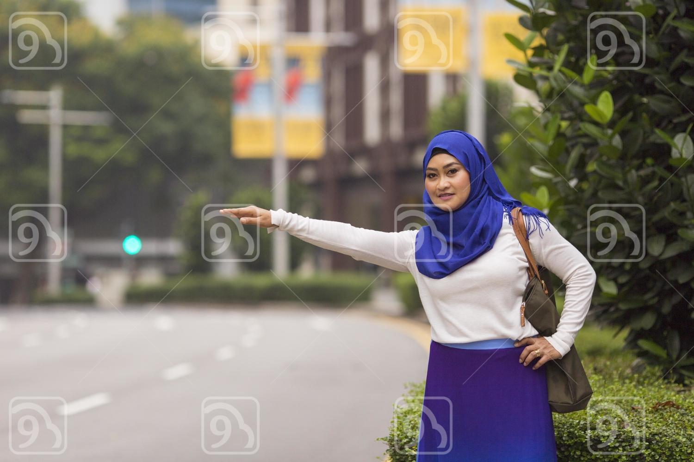 Muslim lady hailing a bus