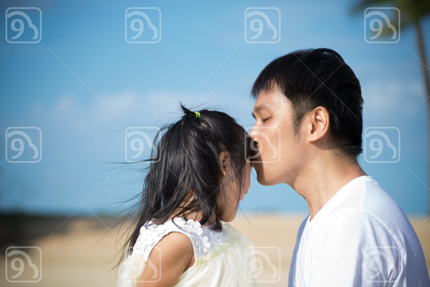 Father kissing his little daughter