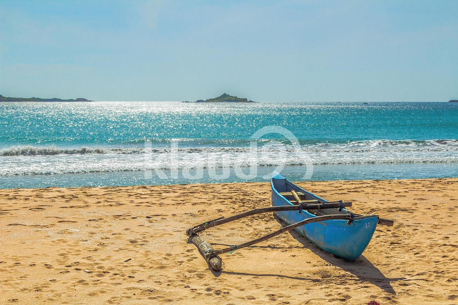 Aboriginal boat on the sandy shores of the Indian Ocean. Sri Lanka