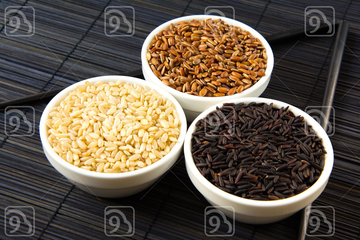 black, red and white unpolished rice on a straw mat