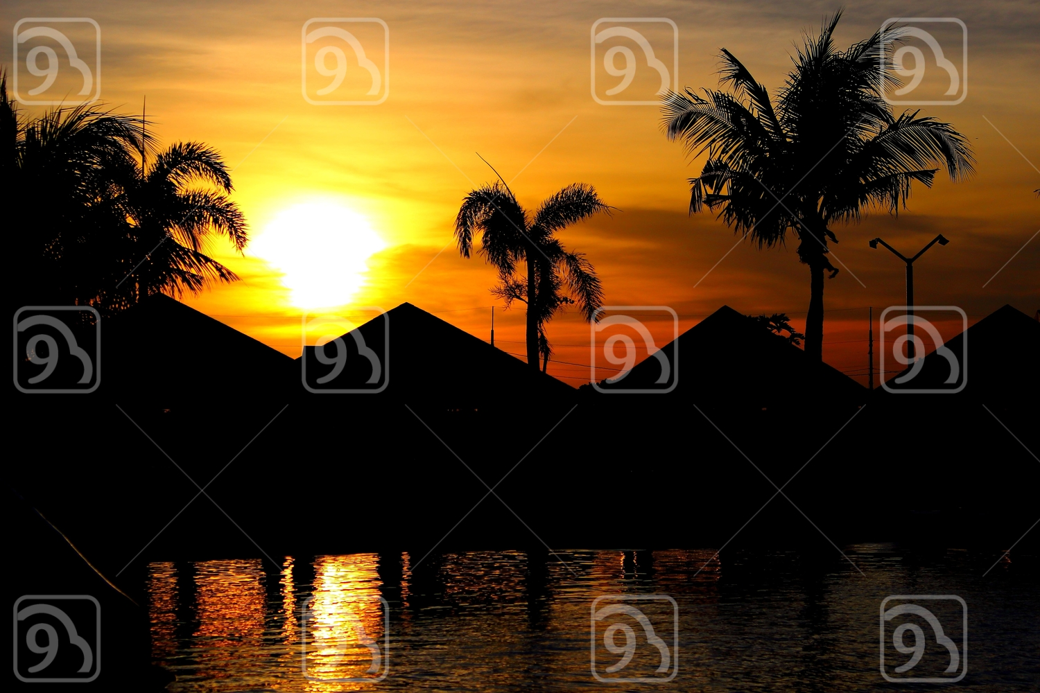 Sunset with silhouettes of huts and palm trees