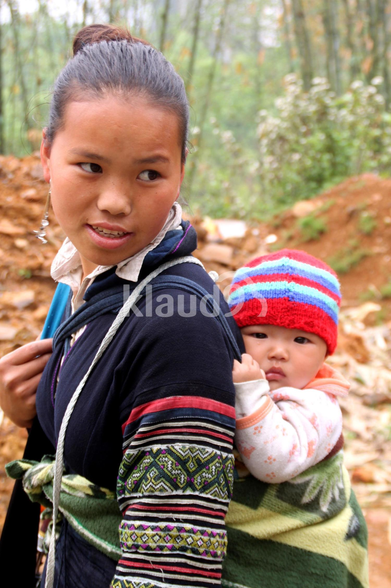 Young girl with baby on back
