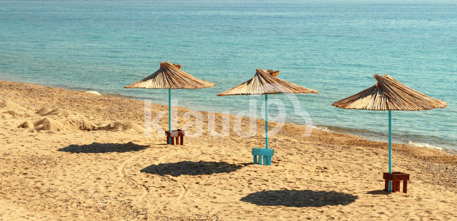 Three sun umbrellas by the beach