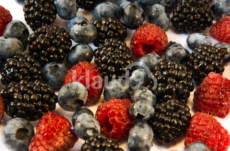 raspberries blackberries blueberries on a table