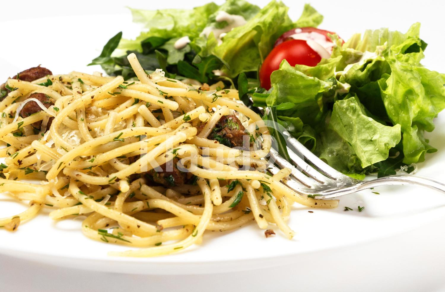 Spaghetti on a white plate with slices of meat and vegetable salad