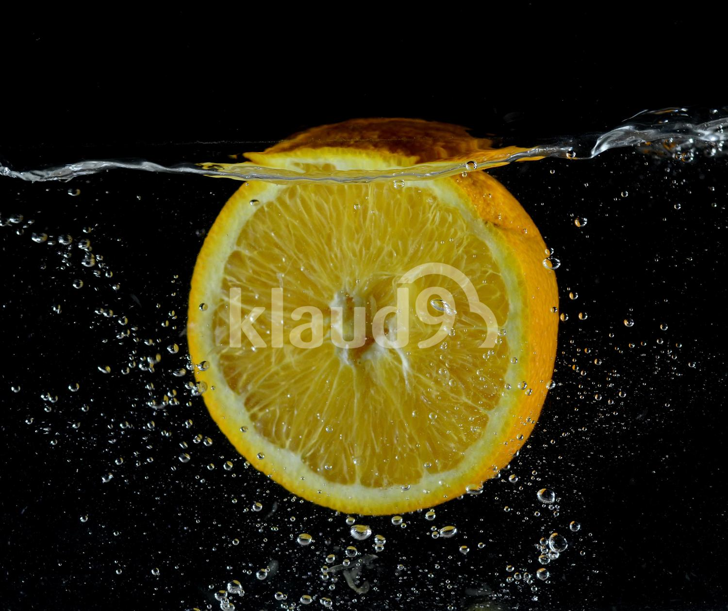 Orange falling into the water, the clash of the fruit with water
