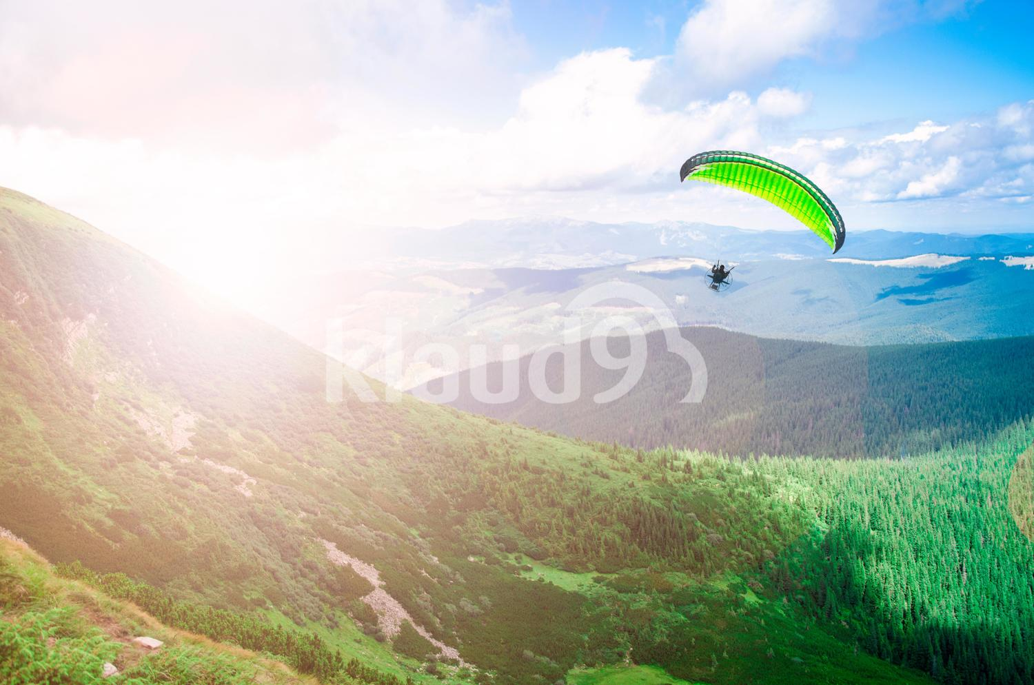 Paraglide silhouette over mountain peaks.