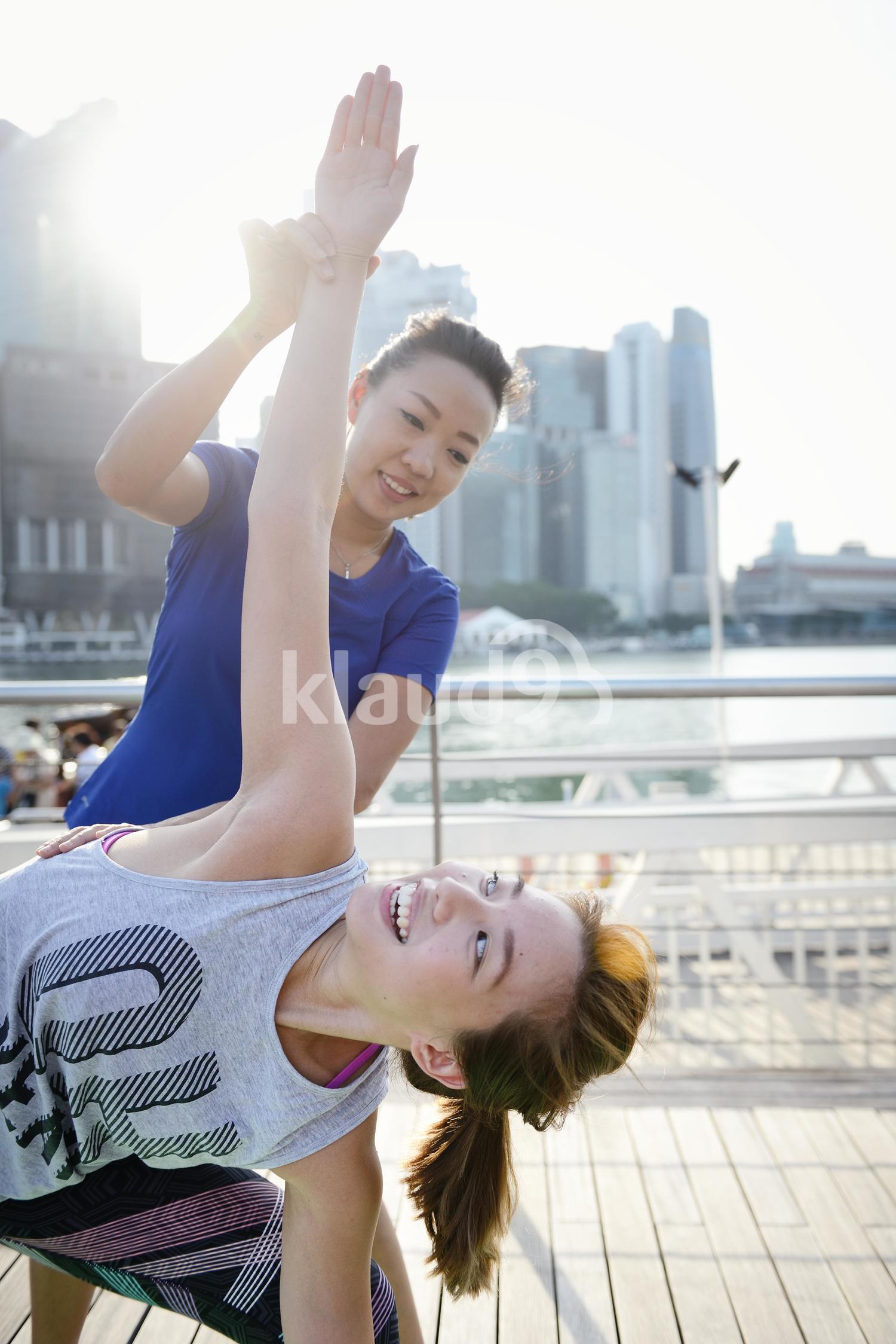 Friends practising Yoga at Marina Bay