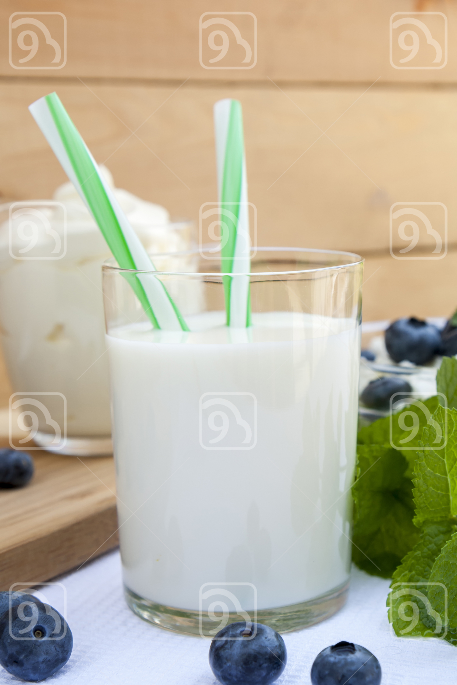 Glass of fresh milk with drinking straw