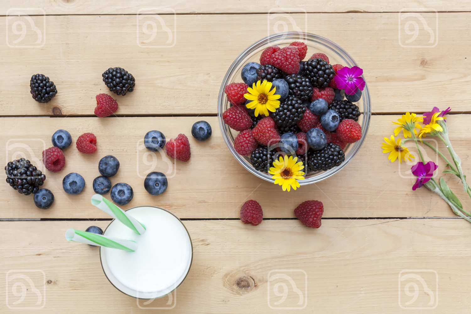 Glass of fresh milk with drinking straw on the table with summer berries
