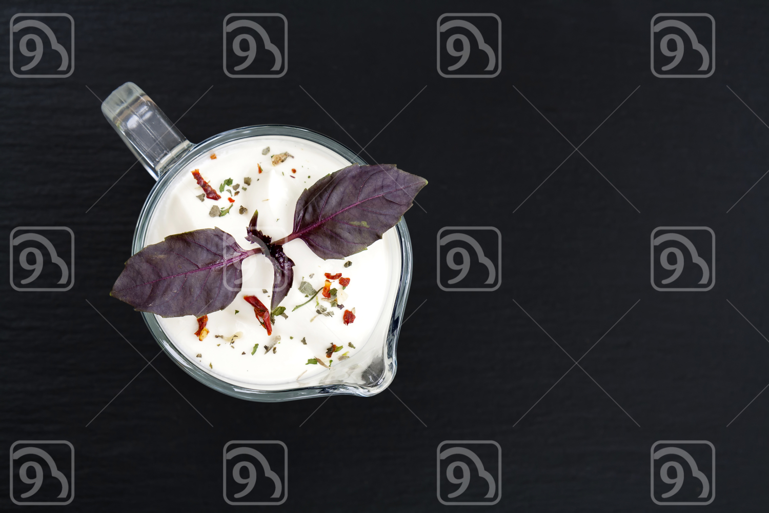 Sour cream in sauce boat with basil and spices