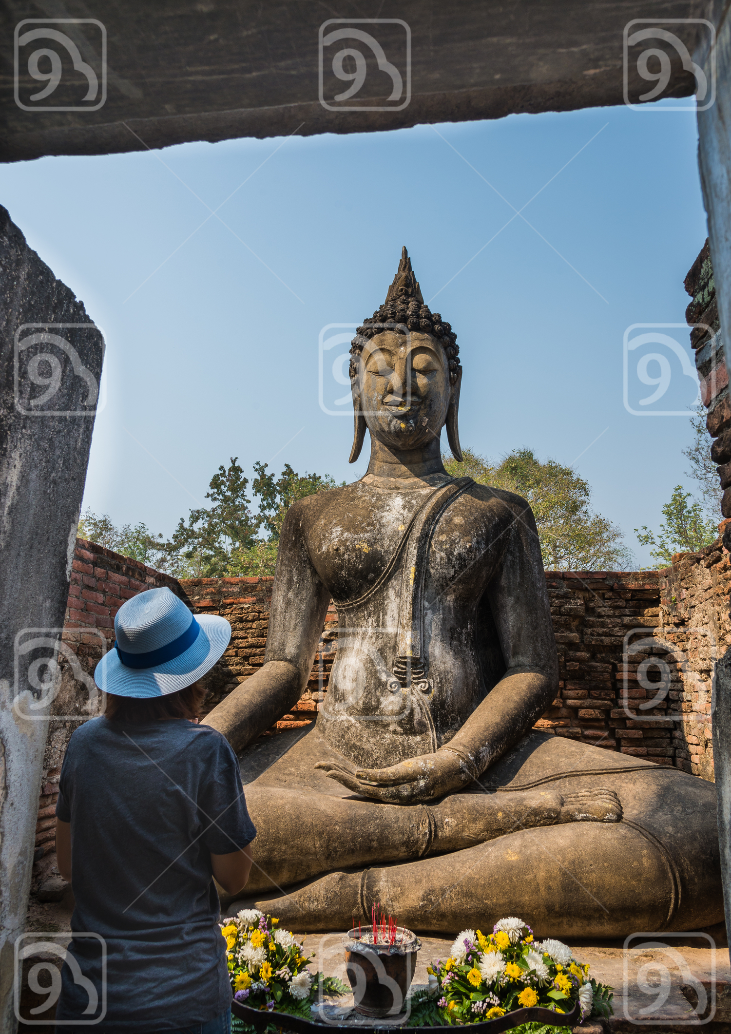 Lady pray sitting Buddha statue in the Ancient temple Thailand