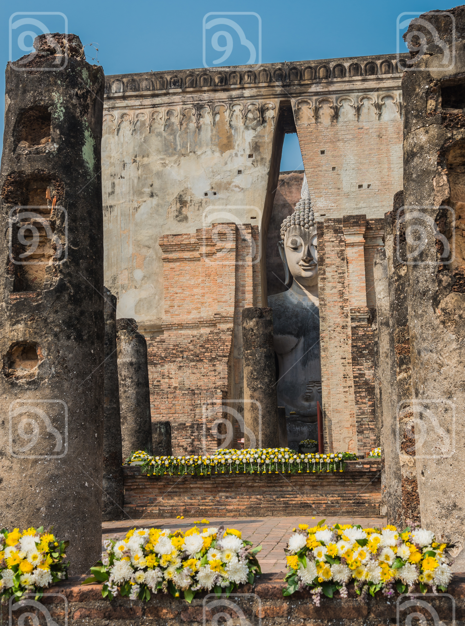 View Old sitting Buddha statue through the gate of ancient temple Thailand