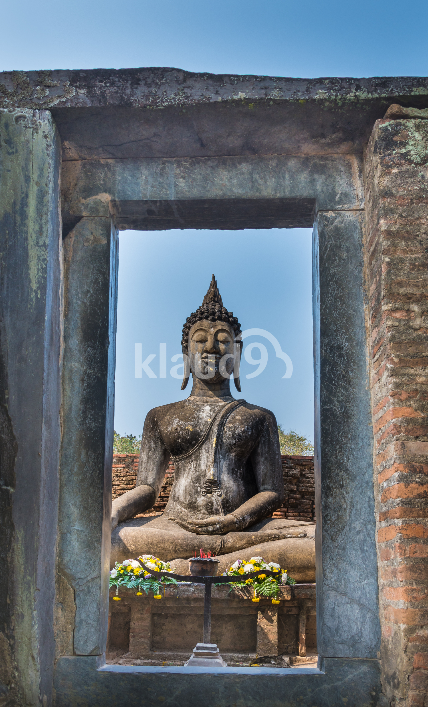 View of Sitting Buddha statue through stone door in the Ancient temple Thailand