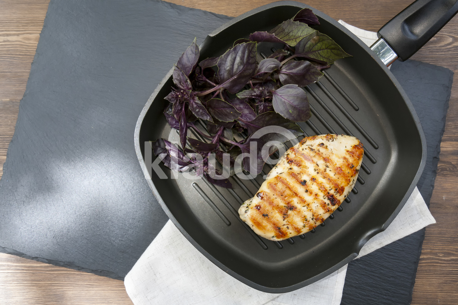 Grilled chicken breast steak with violet basil on teflon pan grill