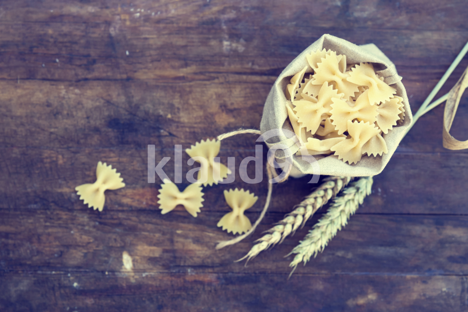 Uncooked Italian pasta farfalle in canvas little bag