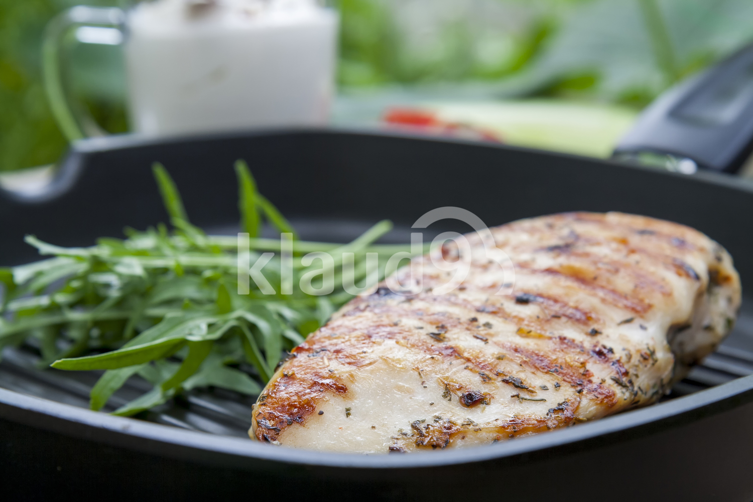 Grilled chicken breast steak with arugula on teflon pan grill