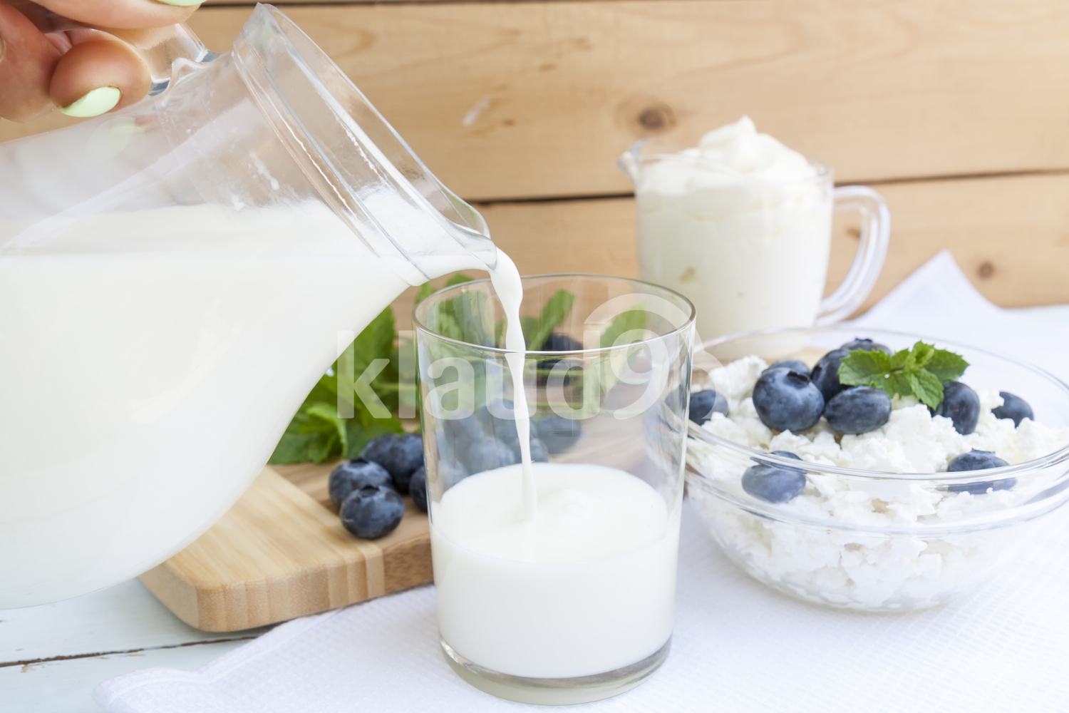 Pouring milk in the glass on the table