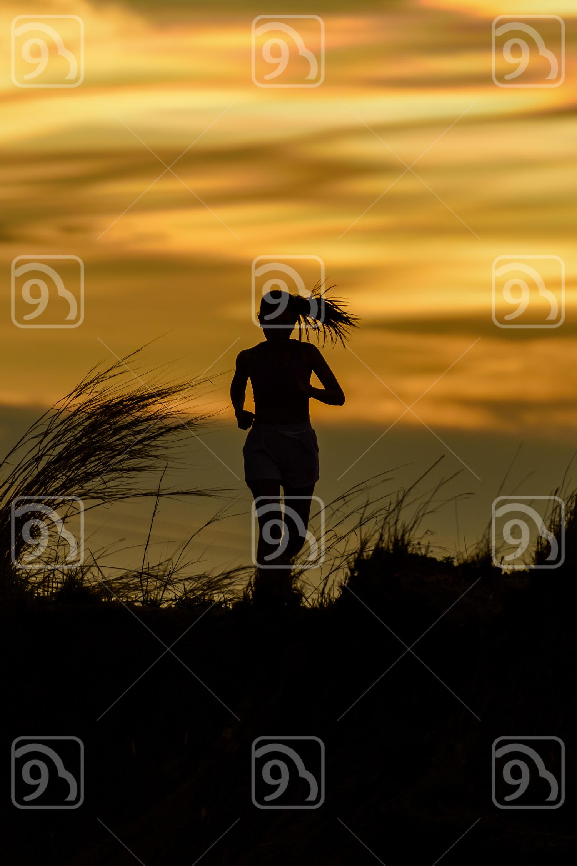 Woman running alone at beautiful sunset