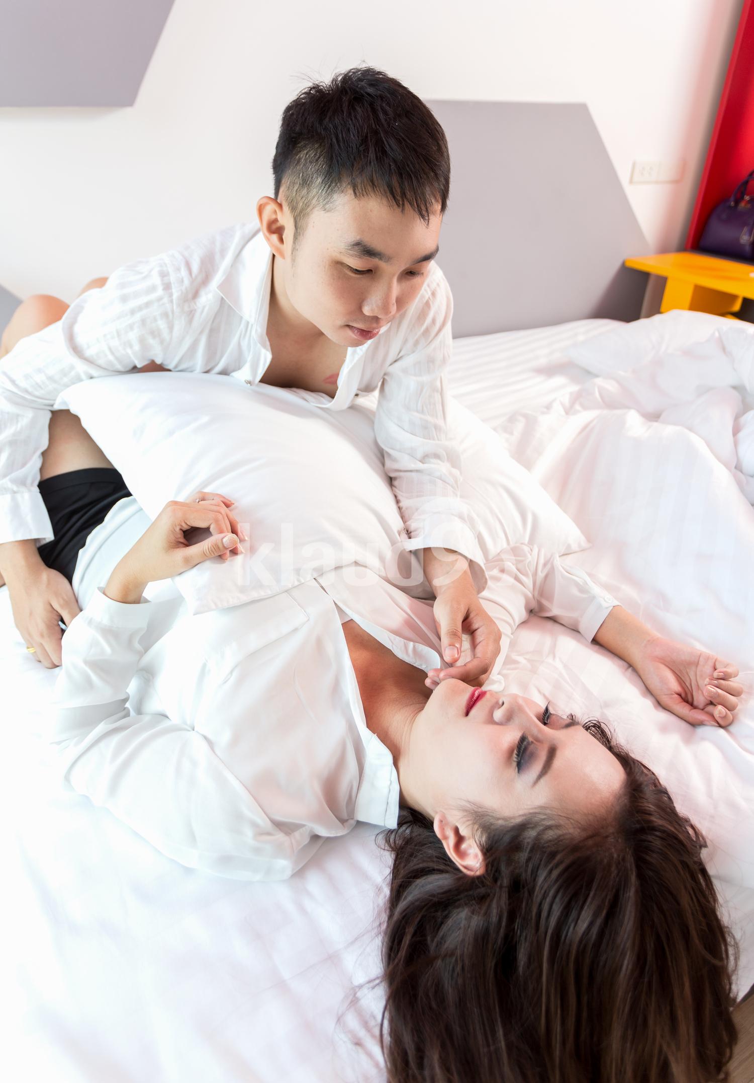 Young adult heterosexual couple lying on bed