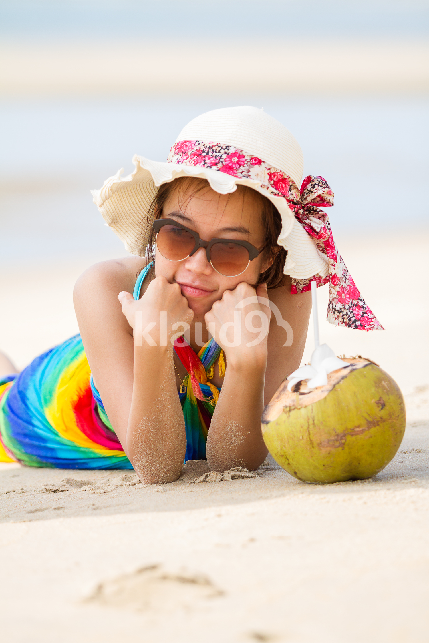 Young woman in swimsuit with coconut cocktail on the beach