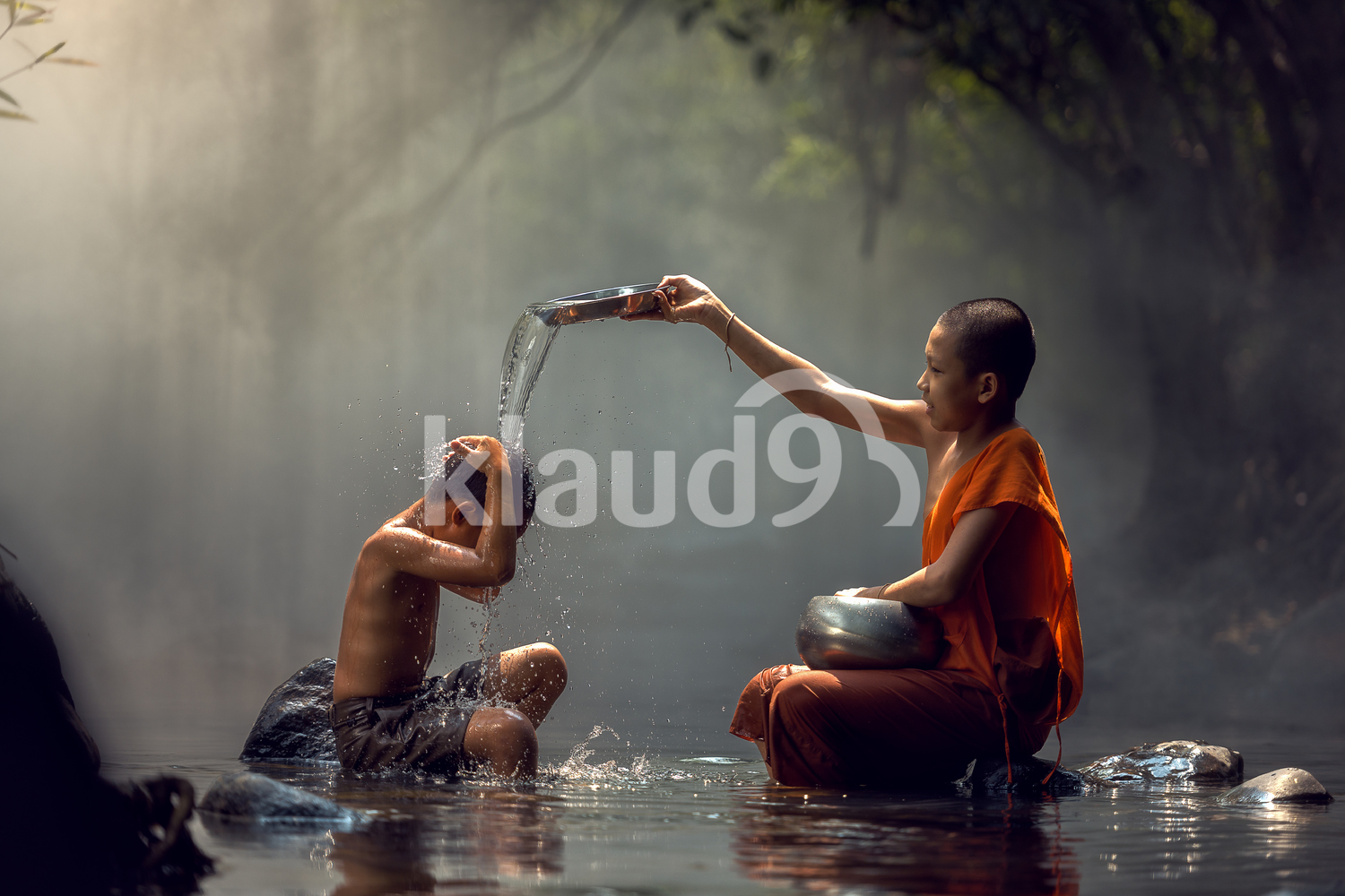 Little monk and child taking a bath at waterfall