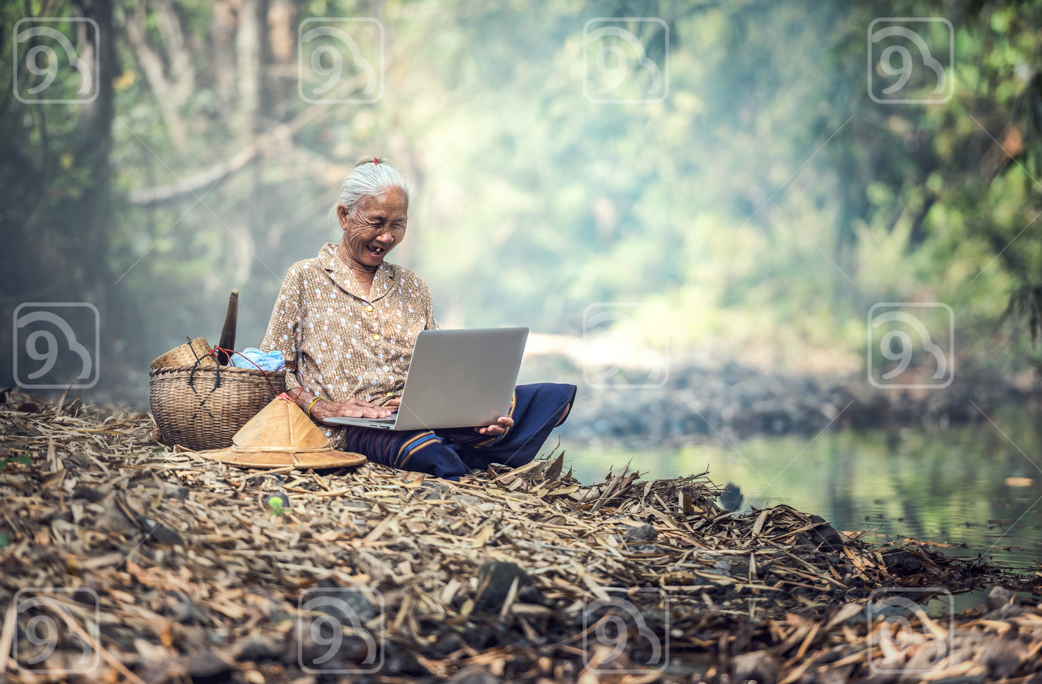 Old woman using a laptop outdoor