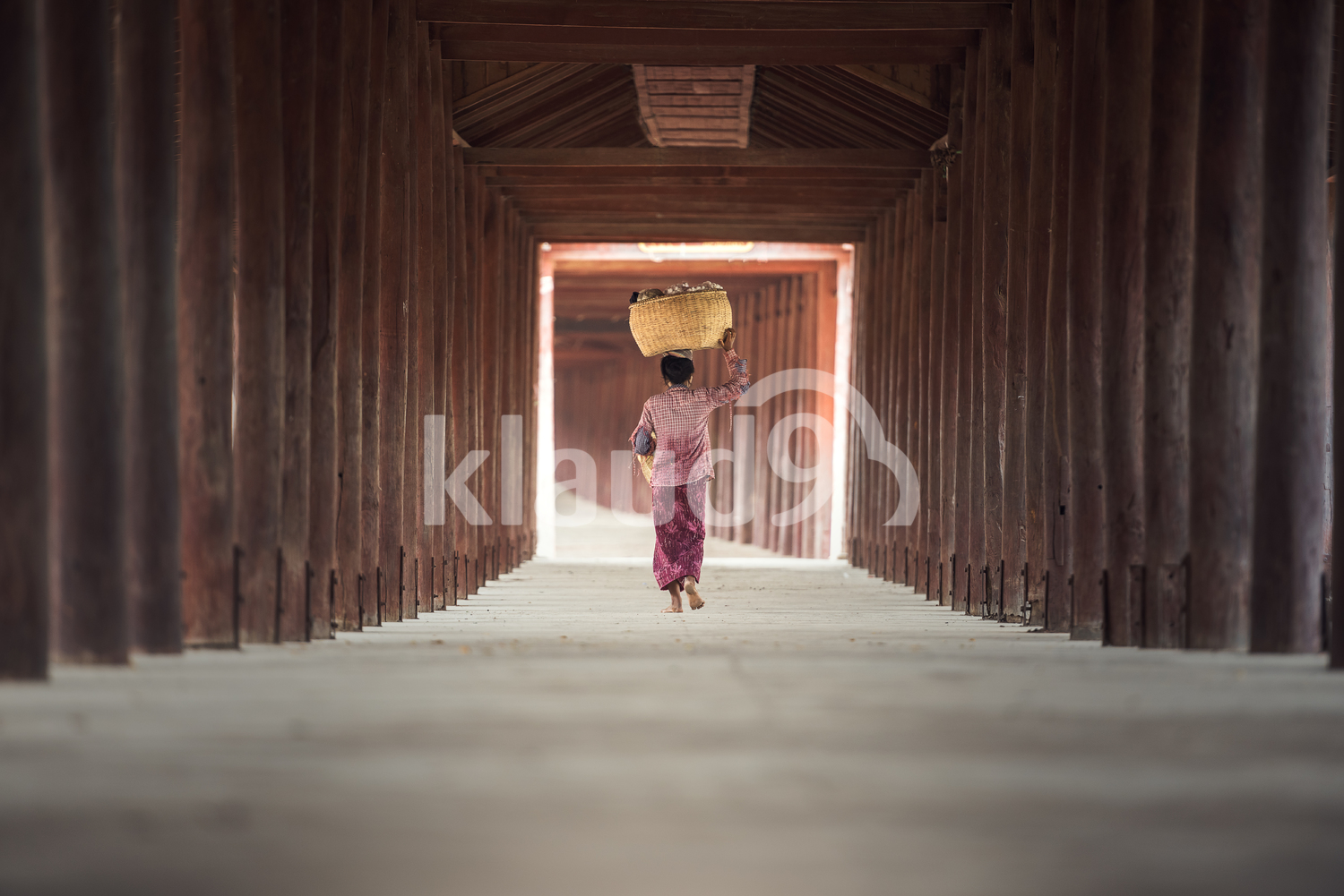 Burmese woman putting bamboo basket on head