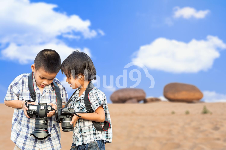 Asian boys holding camera