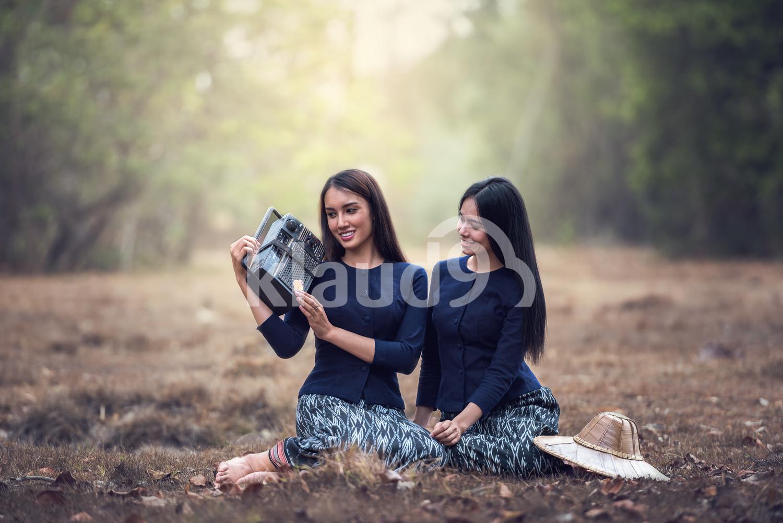 Woman Holding Radio in grass field