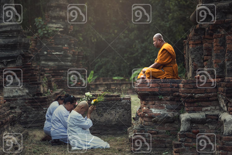 People praying respect to monk