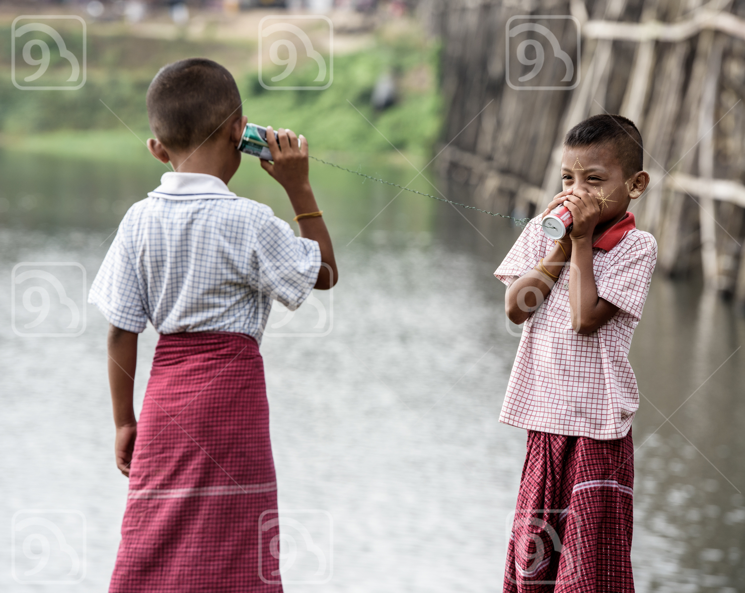 Happy Thai boys talking on a can phone
