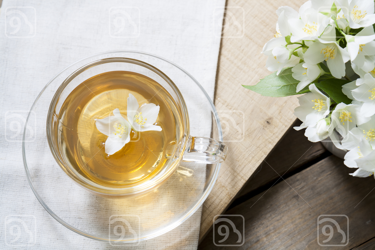 Cup of tea with jasmine and blooming jasmine branch