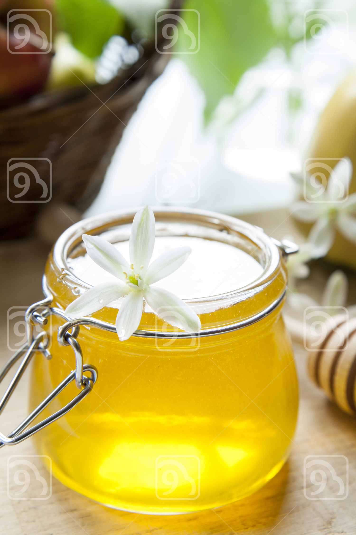 Honey and white flowers on table