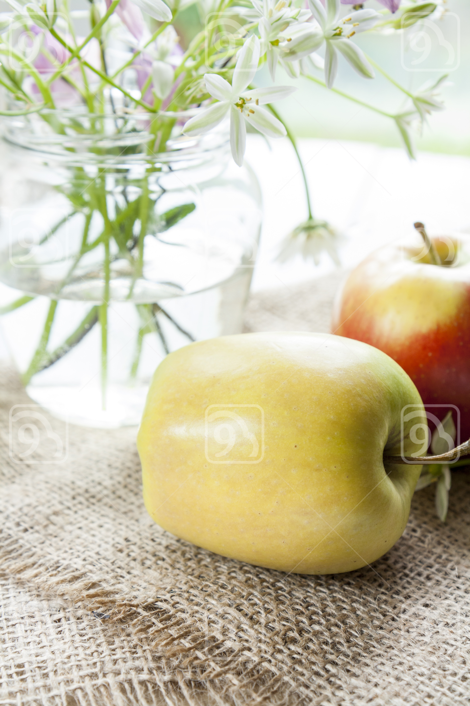 Apples and white flowers on table