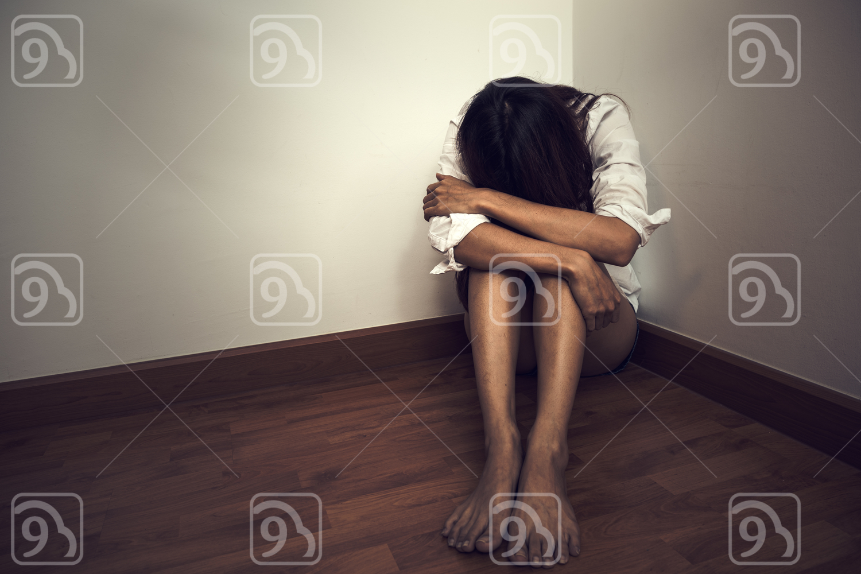 Sad woman sitting alone in  empty room